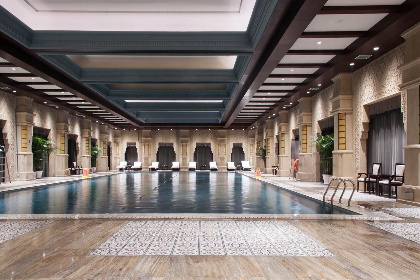 Luxe zwembad in huis met natuursteen en keramisch parket