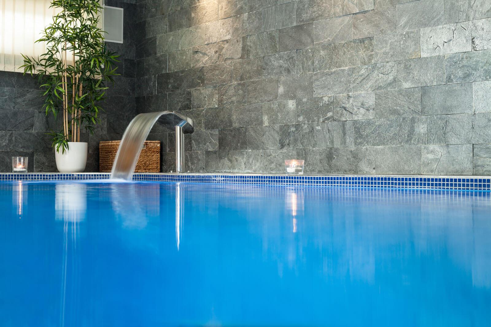Luxe zwembad met natuursteen wand en bad